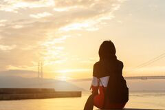 Free Silhouette Alone Young Woman Relax Siting On Riverside Ocean And Watching Sunset And Cloud Sky With Akashi Kaikyo Bridge. Royalty Free Stock Photo - 197591355