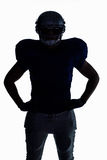 Silhouette American football player standing with hand on hip