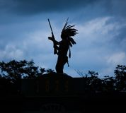 Silhouette of American Indian warrior. Man with feather headdress and tomahawk Stock Photos