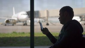 Silhouette american man businessman using phone at the airport looks app in phone. In order to check the gate male traveler business and travel stock footage