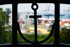Silhouette of an anchor in the fence and sea port. In the foreground closeup you can see the silhouette of an anchor in a metal fence. On the back you can see Stock Photos
