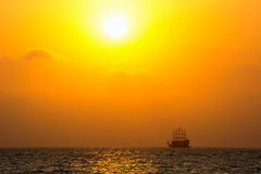 silhouette of the ancient ship at sunset Stock Photos