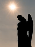 Silhouette of an Angel. In front of a bright sun Royalty Free Stock Photography