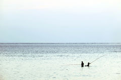 Silhouette of 2 anglers by the shallow sea with blue skyline and water Stock Photography