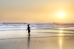 Silhouette of anonymous female child running and playing on amazing beautiful desert beach on sunset with an orange sky and golden Stock Photo