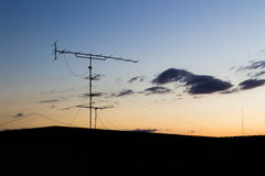Silhouette of antenna. On the roof top of the building at sunset Stock Photos
