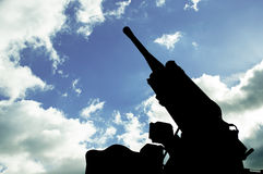 Silhouette of an anti-aircraft cannon on a background of clear s Stock Image