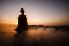Silhouette of Arab man stands alone in the desert and watching the sunset with clouds of fog. Eastern Fairytale Royalty Free Stock Image