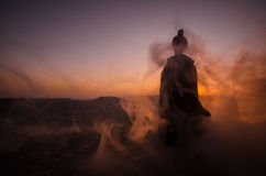 Silhouette of Arab man stands alone in the desert and watching the sunset with clouds of fog. Eastern Fairytale Royalty Free Stock Images