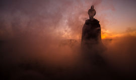 Silhouette of Arab man stands alone in the desert and watching the sunset with clouds of fog. Eastern Fairytale Stock Images