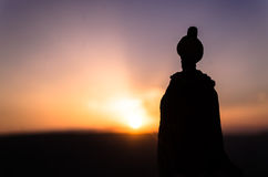 Silhouette of Arab man stands alone in the desert and watching the sunset with clouds of fog. Eastern Fairytale Royalty Free Stock Photos