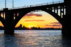 Silhouette of an arched railway bridge on a beautiful sunset on the Dnieper River in the city of Dnipropetrovsk. Dnipro, Dnepr, Dnepropetrovsk Ukraine stock image
