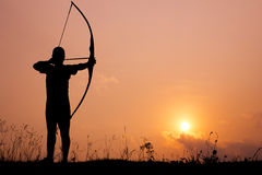 Silhouette archery shoots a bow Stock Photos