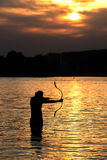 Silhouette archery shoots a bow at a target in sunset sky Stock Photography