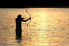 Silhouette archery shoots a bow at a target in sunset sky Stock Photo