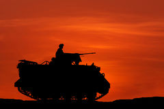 Silhouette armored personnel carrier vehicle on sunset. Background stock photos