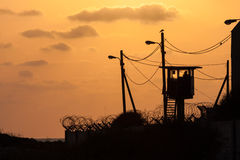 Silhouette of army watchtower behind barbed wires Stock Photography