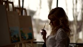 Silhouette of the artist with brush in his hand near the easel in drawing Studio stock video footage