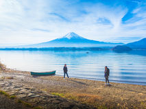 silhouette asia couple traveler 30s to 40s , boy walk to his girlfriend and take picture with boat on ground at side of lake royalty free stock photography