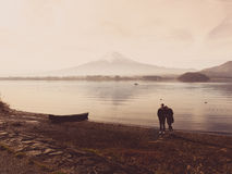 Silhouette asia couple traveler 30s to 40s stand and take picture with boat on ground at side of lake kawaguchi on morning time w. Ith fuji mountain background stock image