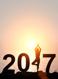 Silhouette Asia woman yoga in Happy new year 2017 tex. T on the beach at sunset stock illustration