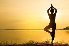 Silhouette Asia woman yoga on sunset. Sunset sky background Royalty Free Stock Photos