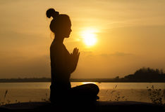 Silhouette Asia woman yoga on sunset Stock Photography