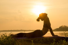 Silhouette Asia woman yoga on sunset Royalty Free Stock Images