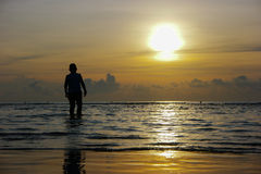 Silhouette of the asian boy standing at the beach during beautif Stock Photos