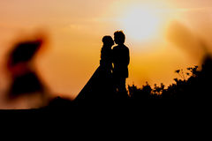 Silhouette of Asian Bride and Groom Standing on Mountain at Sunset Stock Image