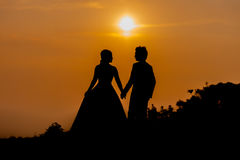 Silhouette of Asian Bride and Groom Standing on Mountain at Sunset Royalty Free Stock Images