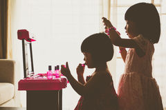 Silhouette Asian Chinese Liitle Sisters Playing With Make-Up Toy Royalty Free Stock Images