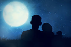 Silhouette of asian couple looking the moon. In the sky at night Stock Photography