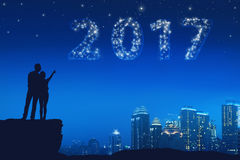 Silhouette asian couple pointing a bright star on a 2017. On the city sky Stock Image