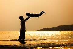 Silhouette of asian father throwing his daughter up in the air stock images
