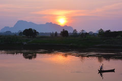 Silhouette of asian fisherman floating in the boat at the sunset Stock Images