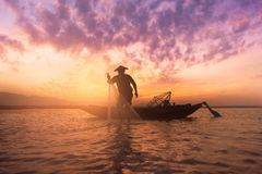 Silhouette asian fisherman holding a net for catching fish Stock Photos