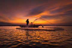 Silhouette of asian fisherman on wooden boat in action Royalty Free Stock Image