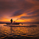 Silhouette of asian fisherman on wooden boat in action Royalty Free Stock Images