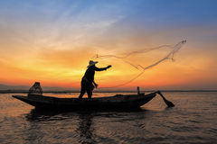 Silhouette of asian fisherman on wooden boat in action Stock Photos