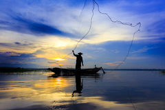 Silhouette asian fisherman on wooden boat casting a net for catc Stock Image