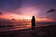 Silhouette of Asian girl on the beach on sunset. Silhouette of Asian girl with dog on the beach on sunset background thailand white alone attractive beautiful royalty free stock photo