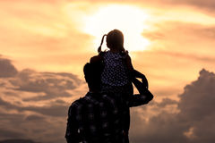 Silhouette asian little girl riding on father& x27;s shoulder Royalty Free Stock Image