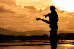 Silhouette asian little girl riding on father& x27;s shoulder Stock Images