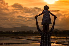 Silhouette asian little girl riding on father& x27;s shoulder Stock Image