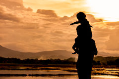 Silhouette asian little girl riding on father& x27;s shoulder Royalty Free Stock Photography