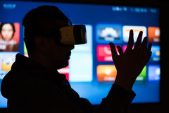Silhouette of asian man wearing virtual reality goggles. In front of screen, selective focus stock image