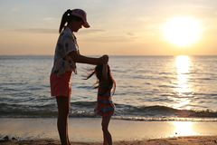 Silhouette Asian mother and daughter standing and playing on the beach at sunset royalty free stock photo