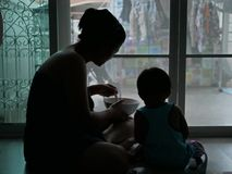 Silhouette of Asian mother holding a bowl of food and feeding her baby at home stock photography
