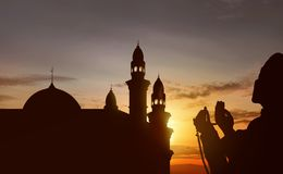 Silhouette of asian muslim praying with prayer beads. At sunset background Stock Photo